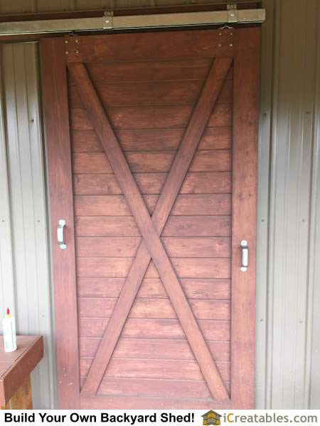 Horse barn door installed on small horse barn for Hanging a sliding barn door