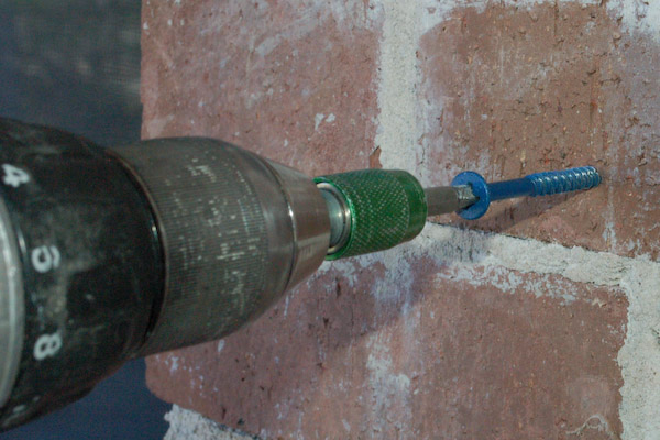 screwing blue screw into concrete