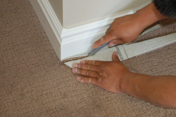 cut carpet at wall with utility knife