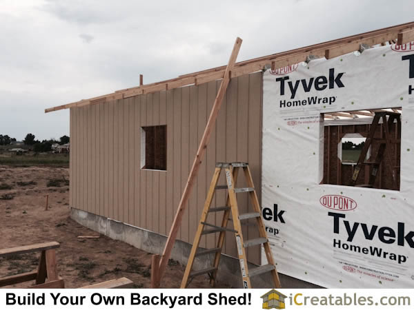 House wrap paper is installed over the O.S.B. and then sheet siding is installed as a wall finish.