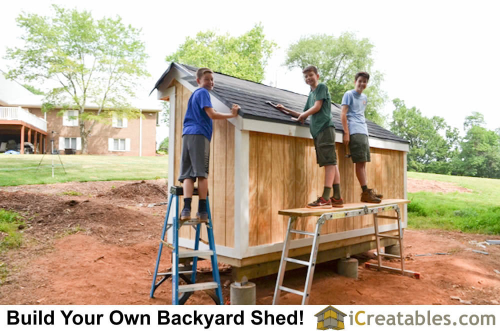 Scouts installing roof shingles on the wood shed plan..