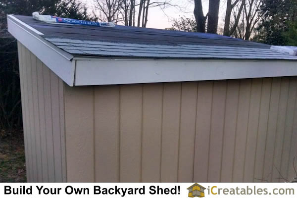 Asphalt shingles are installed on the shed roof.