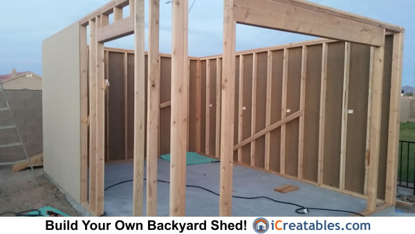 Installing siding on garage door shed walls.