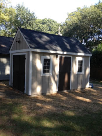 Completed backyard garden storage shed with windows and two doors.