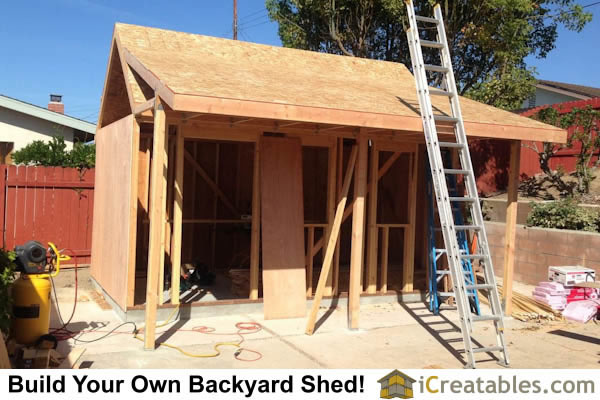 Shed porch framing. Install porch posts and beam. Frame porch roof over the larger shed roof.