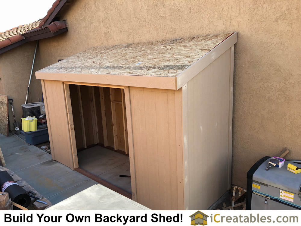 Installed siding and roof sheeting on the shed roof.