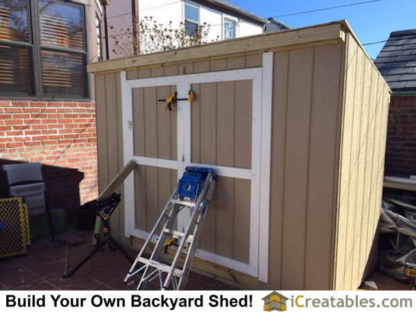 Hanging the shed doors. The doors must be held in place with proper spacing before the hinges are installed.