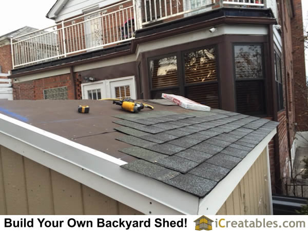 Begin installing asphalt shingles on shed roof.
