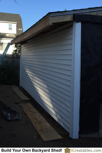 Vinyl siding installed on garden shed walls. Corners are installed first and then the wall.