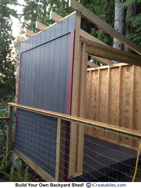 Lean to shed built up against fence. Wall is painted before standing.