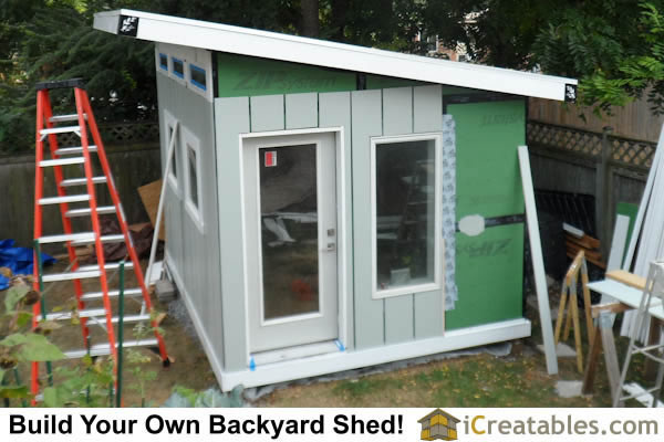 Install cement board siding on shed exterior