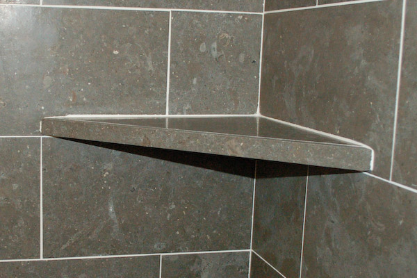 shower corner shelf on top of tile course